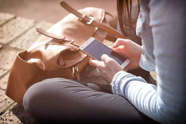 Person sitting on the ground using a smart phone