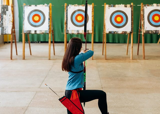 Woman kneeling in front of row of archery targets
