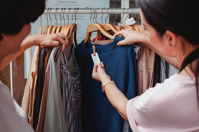 Two people browsing a clothing rack at a store