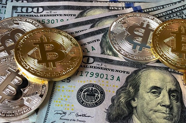 Bitcoins scattered on top of 100 dollar bills
